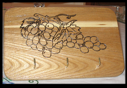 Disegno grappolo uva con pirografo su appendino